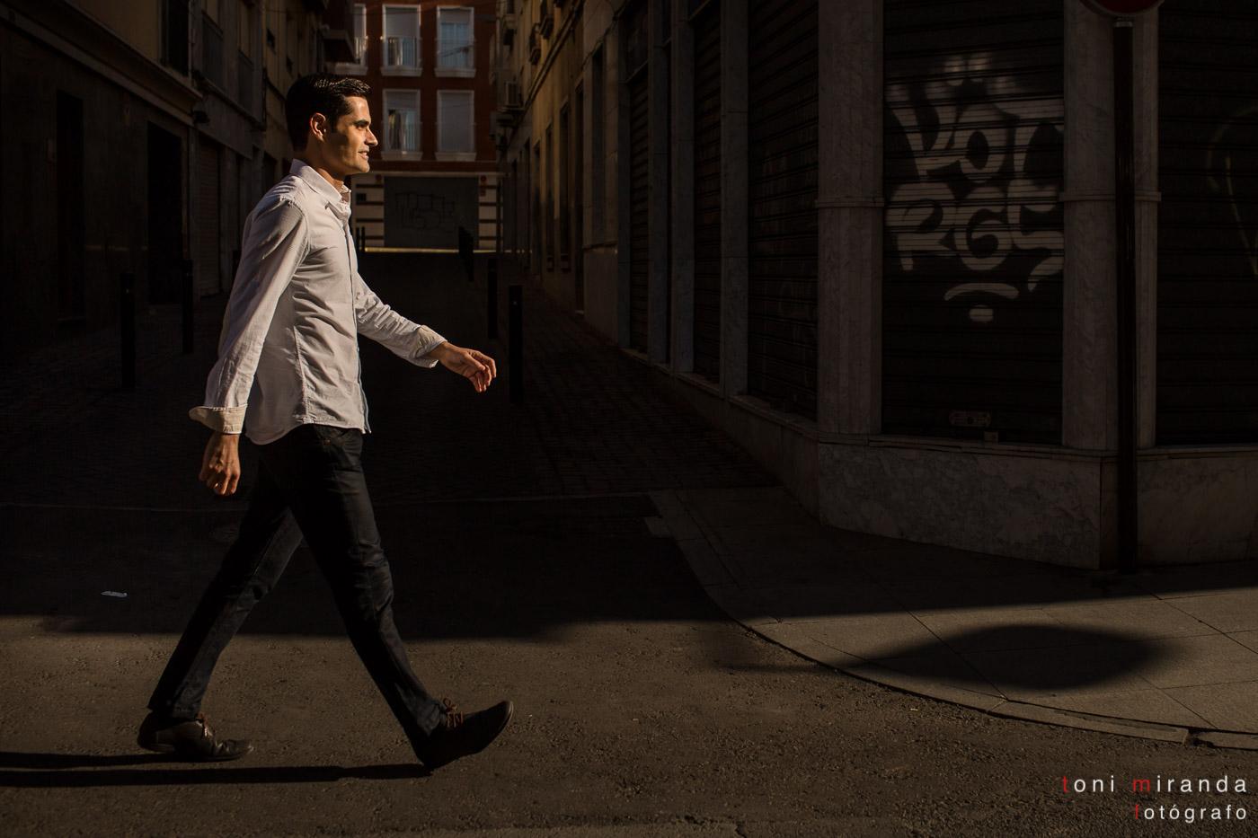 chico caminando por la calle de elche con camisa blanca