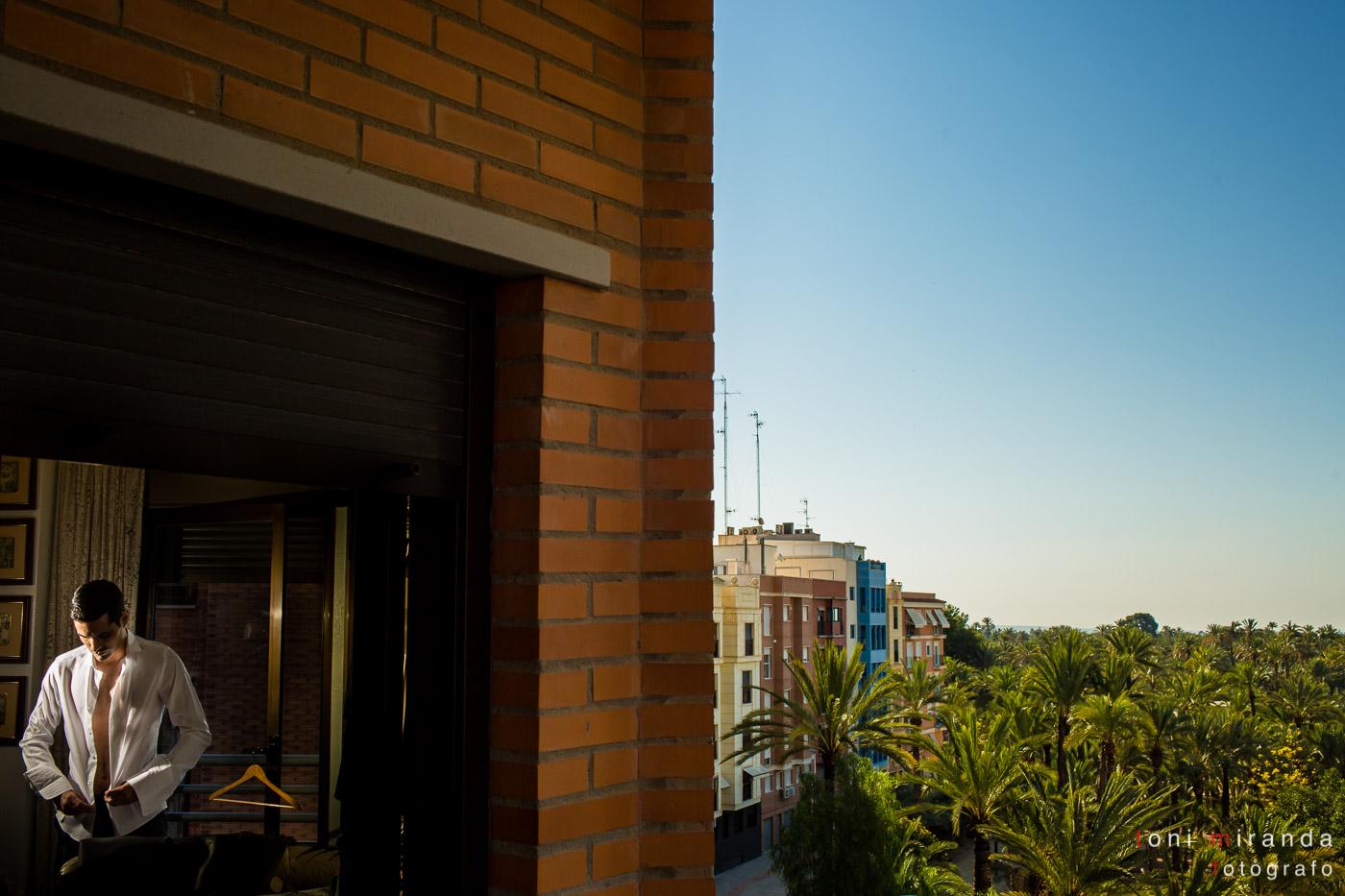 chico a través de la ventana con paisaje de elche con palmeras