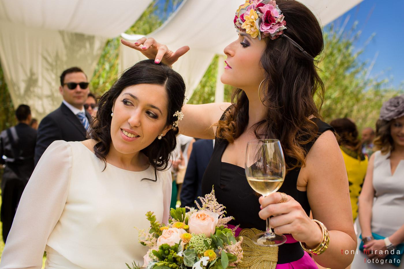 novia con amiga quitándole el arroz tocado de flores copa de vino