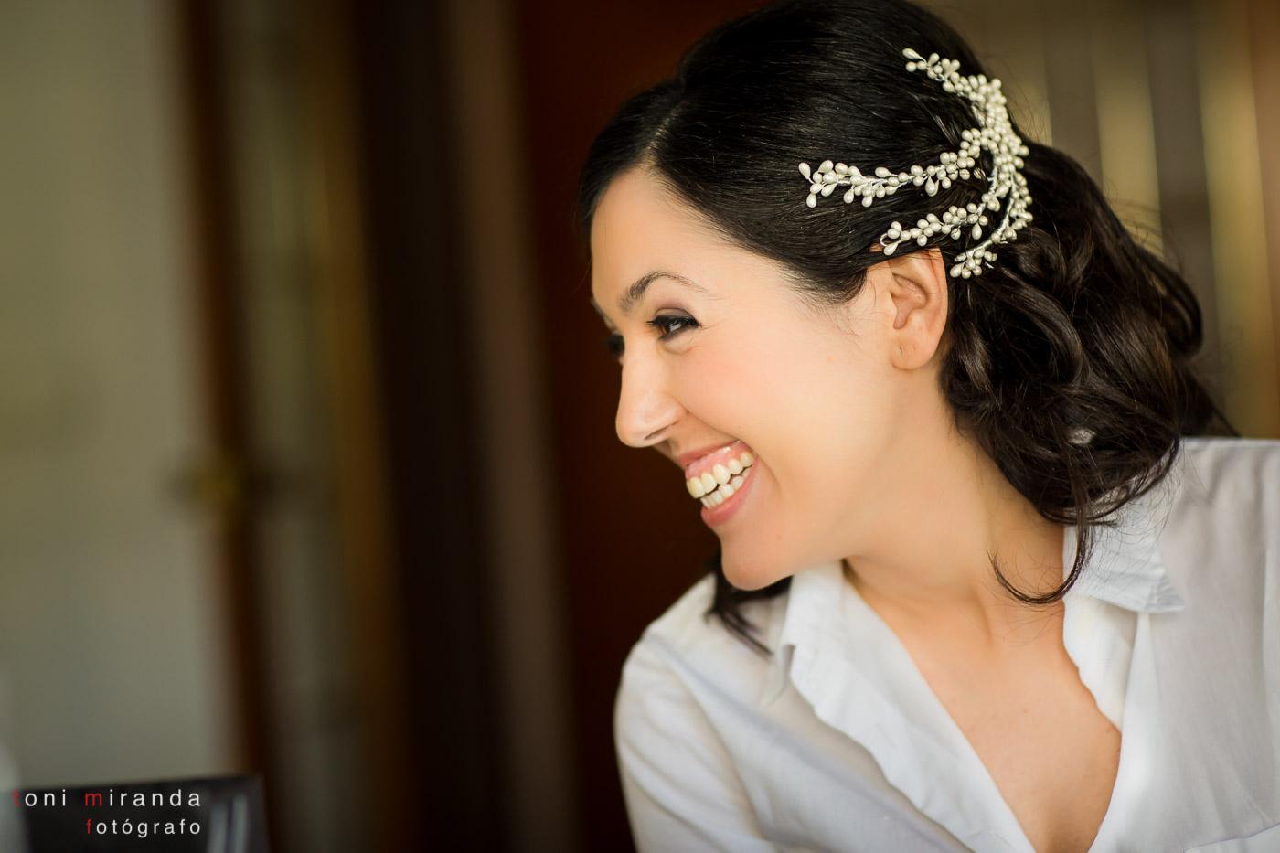novia sonriendo con moño bajo y tocado