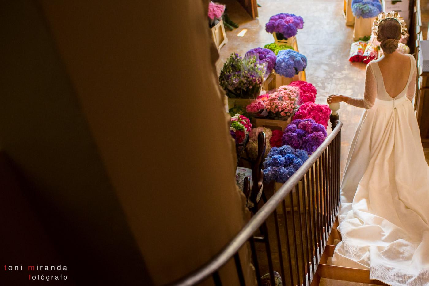 novia bajando escaleras con flores en alquería nova
