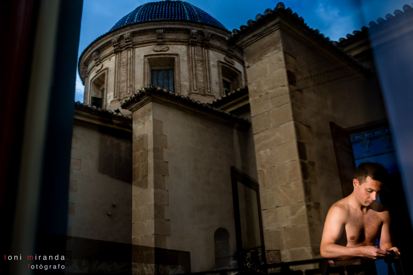 Novio vistiéndose en casa con reflejo de la Basílica de Nuestra señora del Socorro