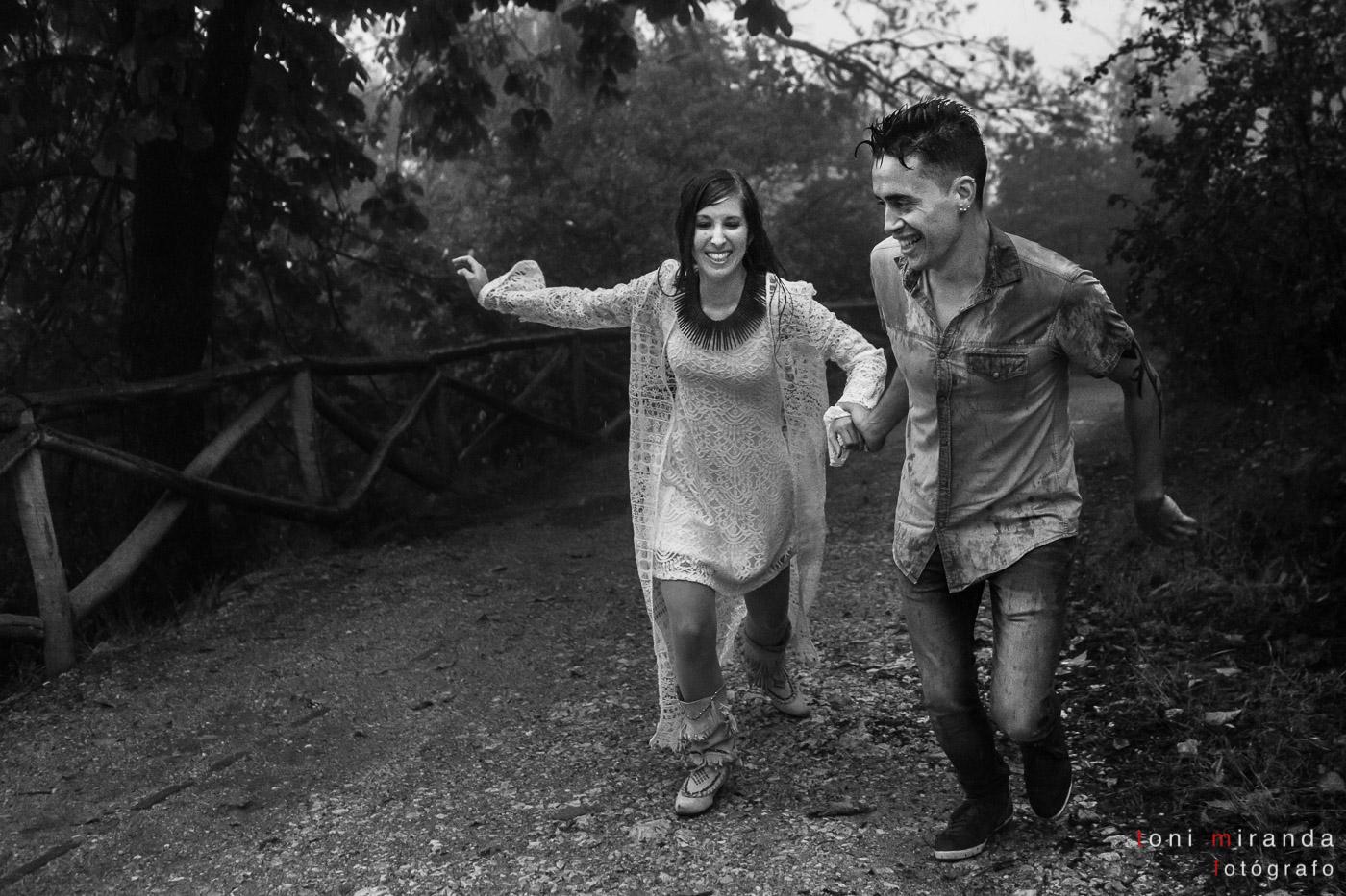 novios corriendo bajo la lluvia en el campo