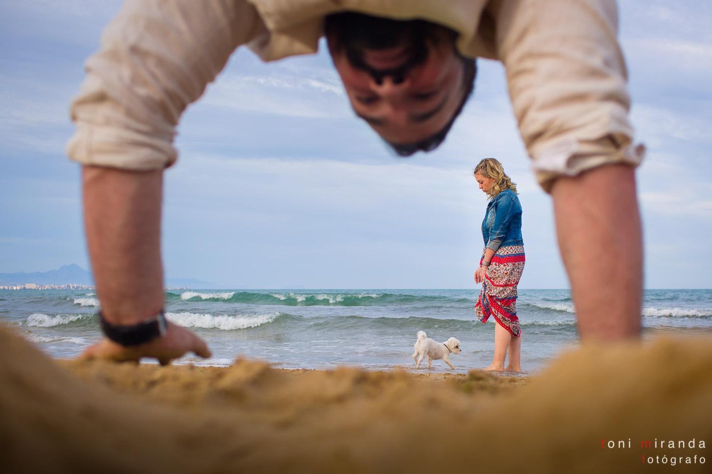 novio haciendo el pino en preboda en la playa